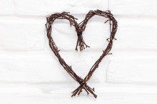 Twigs Heart Against White Bric...