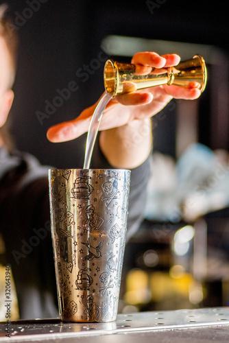 Fototapeta bartender is preparing a cocktail. Bartender pours a cocktail obraz
