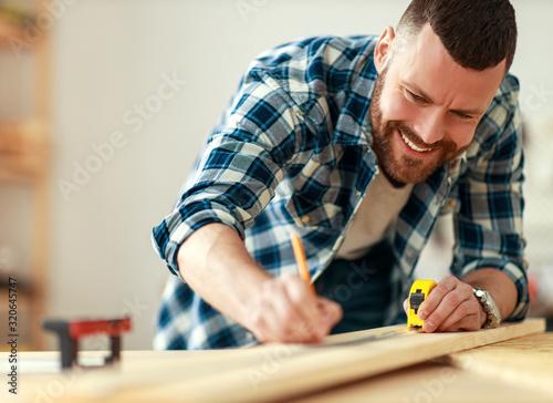 Obraz young male carpenter working in  workshop. - fototapety do salonu