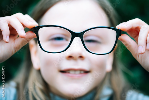 Photo Closeup portrait of little girl  with myopia correction glasses