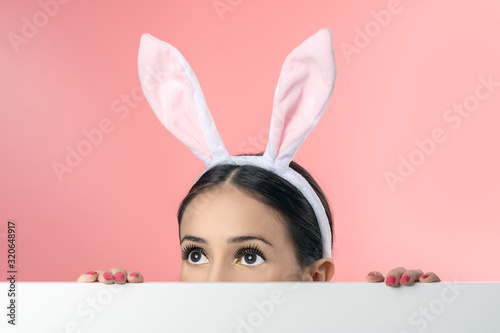 Photo Beautiful young woman with pink bunny ears and blank poster on pink background