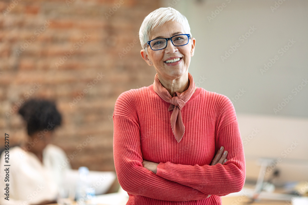 Fototapeta Pretty older business woman, successful confidence with arms crossed in financial building. Cheerful attractive businesswoman crossing arms on chest and looking at camera.