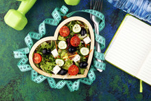 Authentic Fresh Salad In A Wooden Heart Shaped Cup With Dumbbells Excercise Equipment, Measuring Tape On Table. Healthy Lifestyles, Good Health