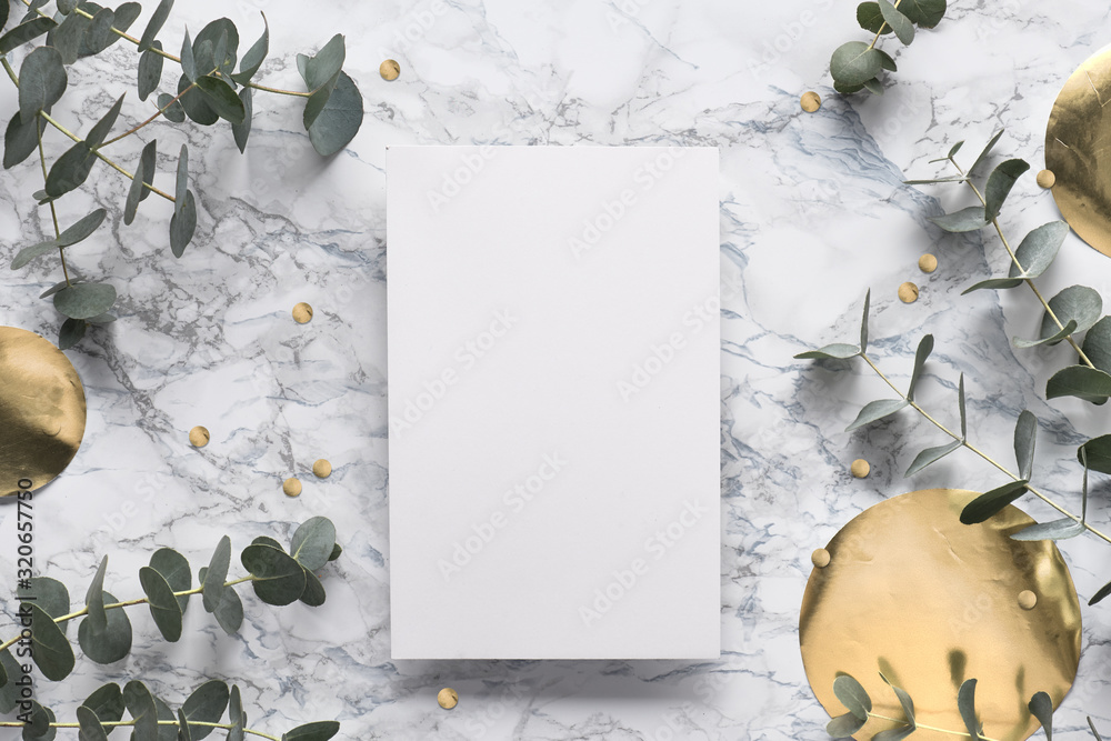 Fototapeta Beautiful abstract floral background. Flat lay, top view eucalyptus on marble background, flat lay on light textured stone table. Trendy background with gold foil circles and confetti.