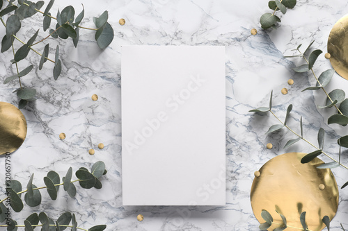 Fototapeta Beautiful abstract floral background. Flat lay, top view eucalyptus on marble background, flat lay on light textured stone table. Trendy background with gold foil circles and confetti. obraz