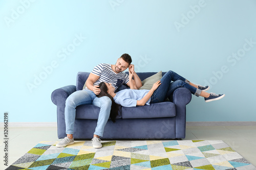 obraz PCV Young couple resting on sofa at home