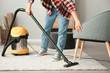 Young Asian man hoovering floor at home