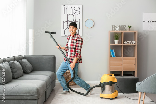 Fototapeta Young Asian man having fun while cleaning floor at home obraz