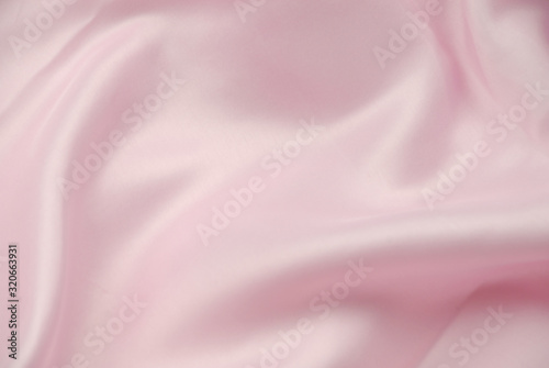Pink satin fabric background. Smooth soft light pink backdrop