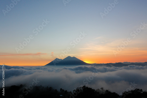 Fotografie, Obraz Sunset over Volcano of Fire and Acatenango Volcano - volcanoes surrounded by clo