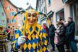 Bajass aus Waldkirch - Narrenfigur in gelb-blauem Gewand zeigt ein traditionälen Gegenstand, bei Fastnachtumzug in Staufen, Süd-Deutschland