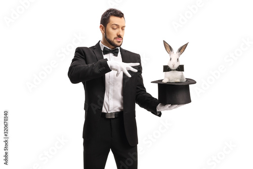 Young male magician making a magic trick with a rabbit in a top hat Fototapeta