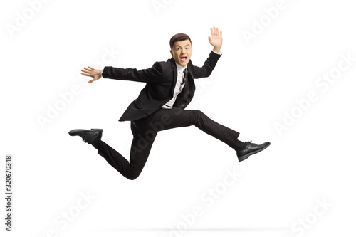 Fototapeta Cheerful young man in a black suit jumping and looking at camera obraz