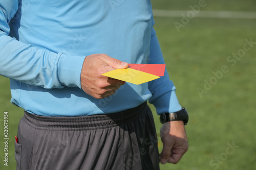 Photo Football referee holding a yellow and red card