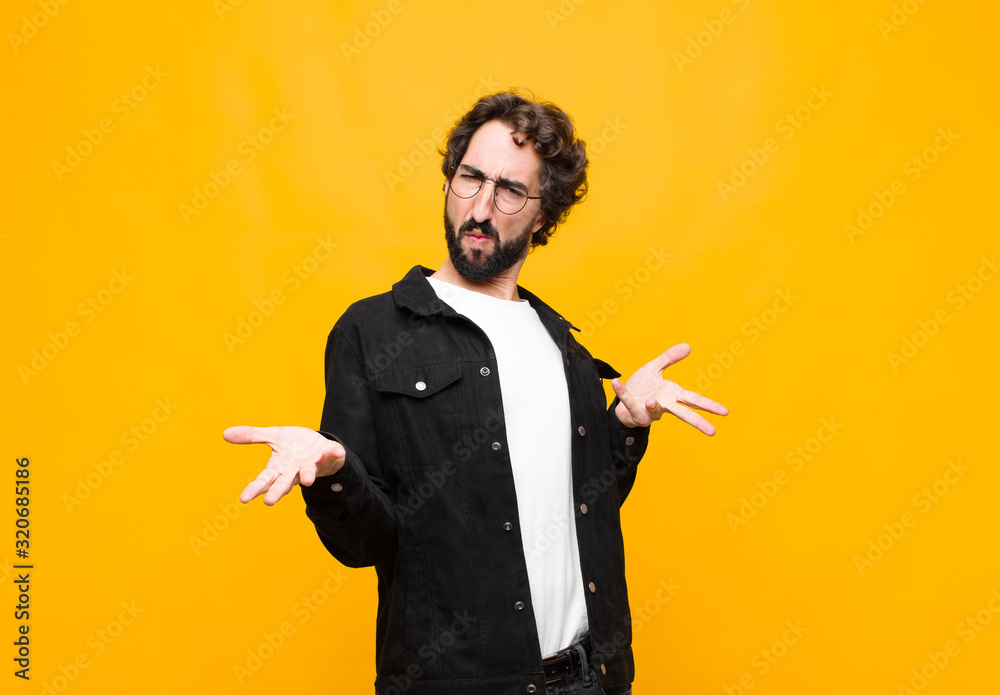 Fototapeta young crazy handsome man feeling clueless and confused, having no idea, absolutely puzzled with a dumb or foolish look against orange wall