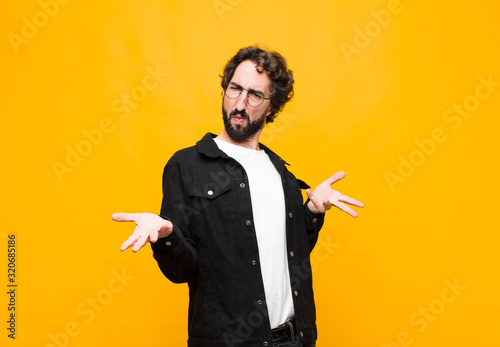 Fototapeta young crazy handsome man feeling clueless and confused, having no idea, absolutely puzzled with a dumb or foolish look against orange wall obraz