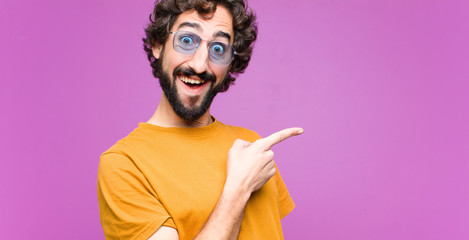 young crazy cool man looking excited and surprised pointing to the side and upwards to copy space against flat wall