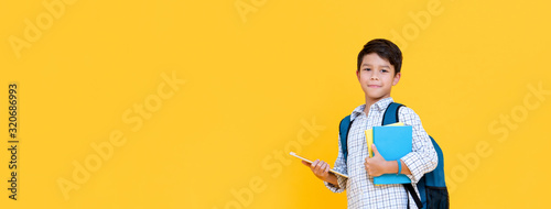 Handsome schoolboy with backpack holding books and tablet computer on banner bac Fototapete