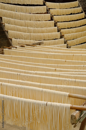 Obraz na plátně Racks of raw noodles hanging outside to dry in Fuli near Yangshuo China