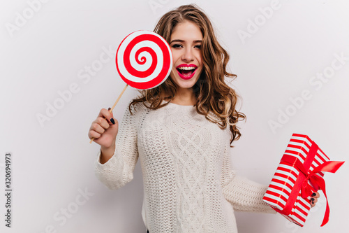Fototapeta Refined curly woman holding sweet candy and birthday present isolated on white background