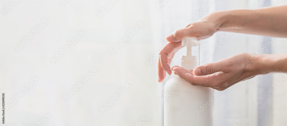 Fototapeta Woman hands pushing pump plastic soap bottle on white background with copy space