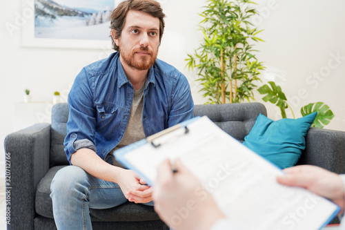 Leinwand Poster Psychologist doctor taking notes during psychotherapy session