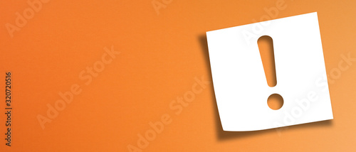 Photo Note paper with exclamation mark on panoramic orange background