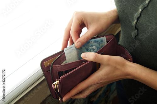 Fotomural Women's hands choose the Ukrainian hryvnia in cash wallet.