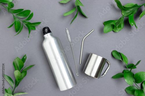 Fototapeta Metal bottle, mug, tube and cleaning brush. Frame made of green leaves on dark gray background. obraz