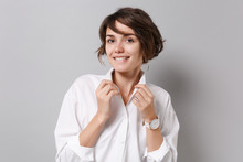 Smiling Beautiful Young Business Woman In White Shirt Posing Isolated On Grey Wall Background Studio Portrait. Achievement Career Wealth Business Concept. Mock Up Copy Space. Straightening Collar.