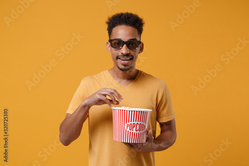 Handsome young african american guy in 3d imax glasses posing isolated on yellow orange background in studio фототапет
