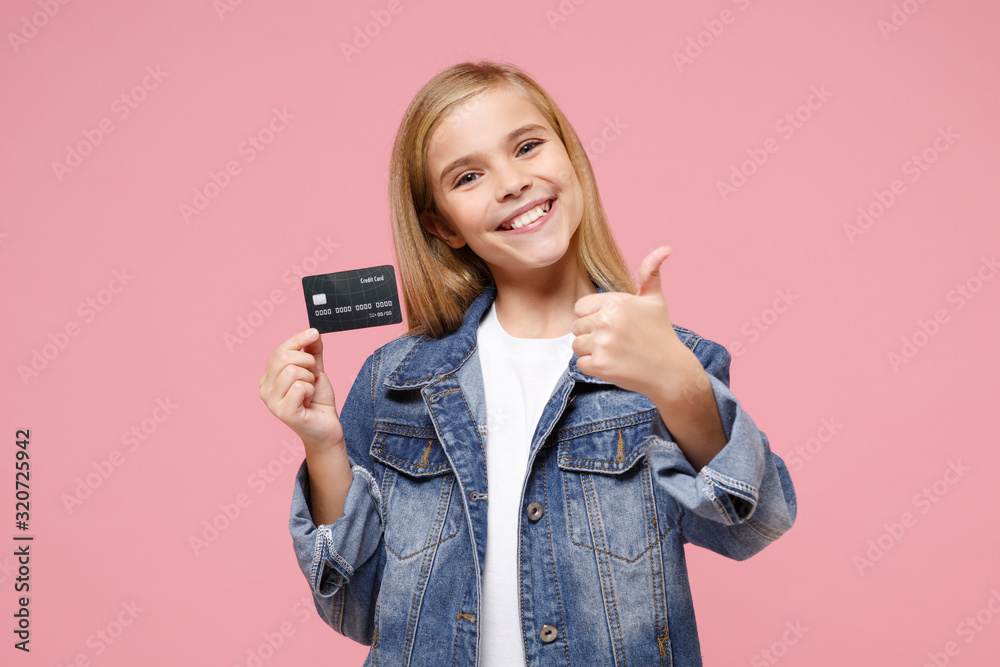 Fototapeta Smiling little blonde kid girl 12-13 years old in denim jacket posing isolated on pastel pink wall background. Childhood lifestyle concept. Mock up copy space. Showing thumb up, hold credit bank card.
