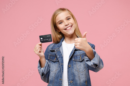 Obraz Smiling little blonde kid girl 12-13 years old in denim jacket posing isolated on pastel pink wall background. Childhood lifestyle concept. Mock up copy space. Showing thumb up, hold credit bank card. - fototapety do salonu
