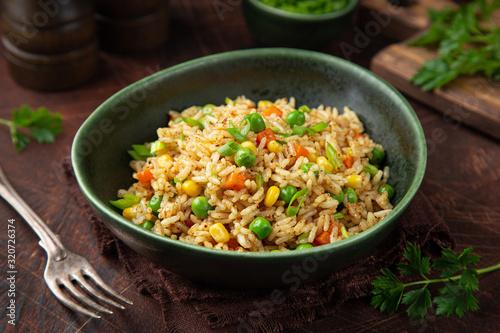 Fototapeta fried rice with vegetables in green bowl obraz