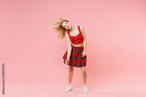 Cheerful young blonde woman girl in red sexy clothes posing isolated on pastel pink wall background studio portrait Wallpaper Mural