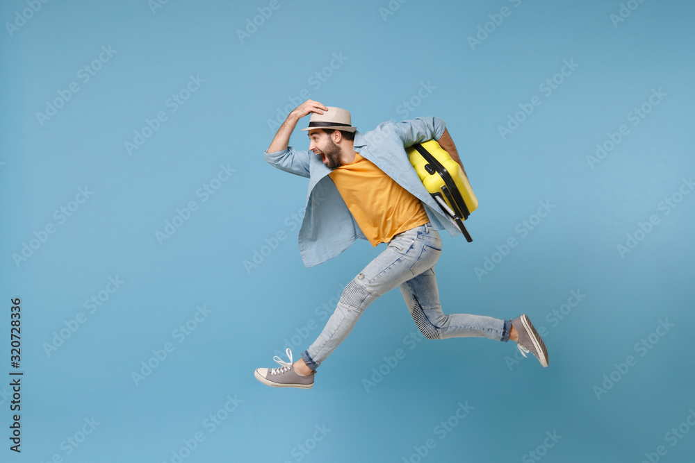 Fototapeta Side view of excited traveler tourist man in yellow clothes isolated on blue background. Male passenger traveling abroad on weekends. Air flight journey concept. Jumping like running, hold suitcase.