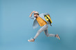 canvas print picture - Side view of excited traveler tourist man in yellow clothes isolated on blue background. Male passenger traveling abroad on weekends. Air flight journey concept. Jumping like running, hold suitcase.