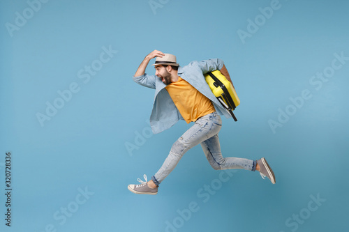 Foto Side view of excited traveler tourist man in yellow clothes isolated on blue background