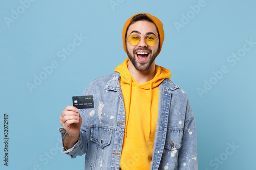 Photo Cheerful young hipster guy in fashion jeans denim clothes posing isolated on pastel blue wall background studio portrait