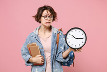 Confused Young Woman Student In Denim Clothes Eyeglasses, Backpack Posing Isolated On Pastel Pink Background. Education In High School University College Concept. Mock Up Copy Space. Hold Books Clock.