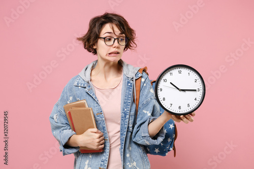 Fotografía Confused young woman student in denim clothes eyeglasses, backpack posing isolated on pastel pink background