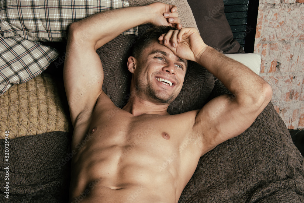 Fototapeta Athletic man resting at home. Morning.