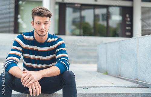 Obraz Handsome young man sitting on stairs - fototapety do salonu