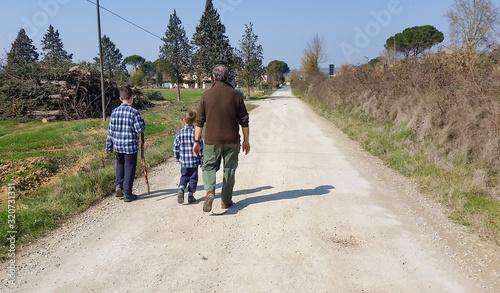 Fényképezés due nipoti vestiti uguali a passeggio con il nonno