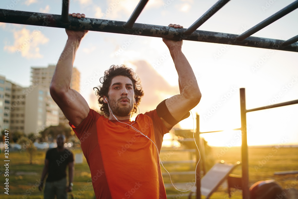 Fototapeta Portrait of a young crossfit sportsman exercising on bar, doing pull-ups for arms and back muscles at the outdoor gym park