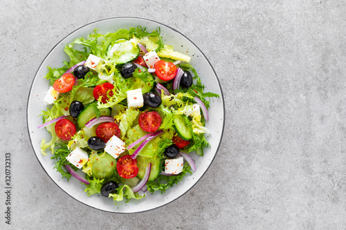 obraz PCV Salad with fresh raw vegetables, cucumber, tomato, olive, onion, lettuce and feta cheese, greek cuisine, healthy food, top view.