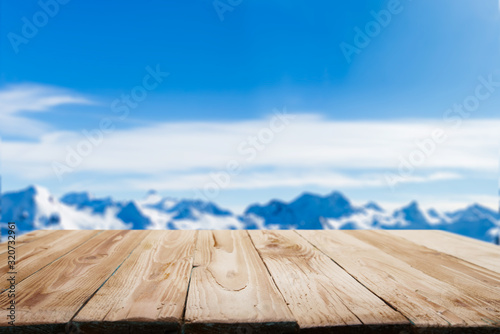 fototapeta na szkło Empty wooden surface on blurry background of snowy mountainous area on winter day and blue sky.