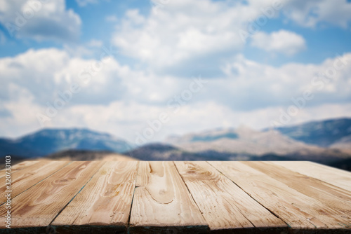 fototapeta na szkło Empty wooden surface on blurry background of snowy mountainous area on winter day and blue cloudy sky.
