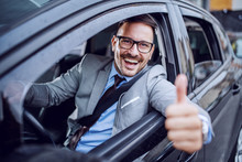 Handsome Caucasian Unshaven Classy Businessman In Suit And With Eyeglasses Holding Hand On Steering Wheel And Giving Thumbs Up.