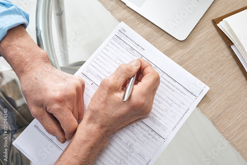 Fototapeta Hands of contemporary senior retired man with pen filling in health insurance form while sitting by table obraz